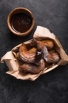 Churros in un sacco di carta con zucchero e salsa di cioccolato sul nero