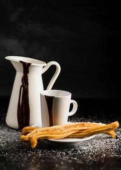 Churros su piastra e contenitori riempiti con cioccolato