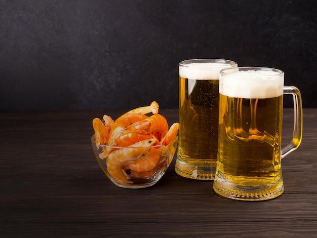 Ci sono due bicchieri di birra leggera su nero, con gamberetti