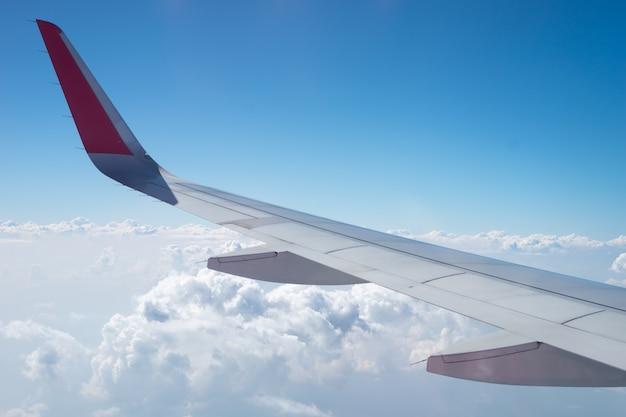 Ci sono molte nuvole bianche tra il cielo blu. questa vista è dalla finestra sull'aereo.