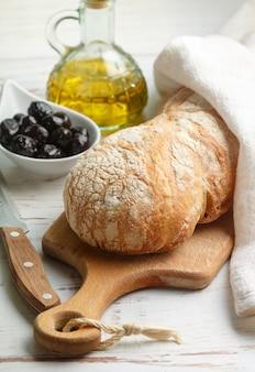 Ciabatta con olive, fresco delizioso pane tradizionale italiano, olive e olio d'oliva su un tavolo di legno bianco