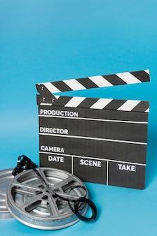 Ciak con bobina di film e strisce di pellicola su sfondo blu