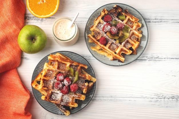 Cialde belghe, caffè, yogurt, frutti su un fondo di legno bianco, concetto della prima colazione.