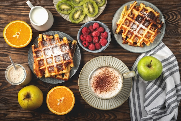 Cialde, caffè, yogurt, frutti e bacche belgi su un fondo di legno, concetto della prima colazione.