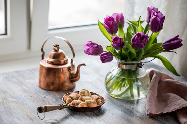 Cialde con miele su un tavolo di legno con fiori vicino alla finestra.