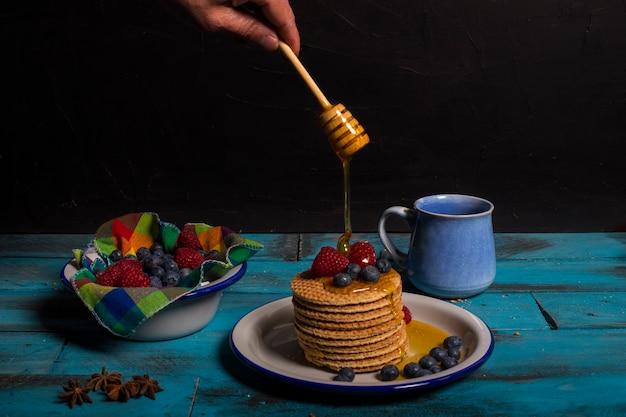 Cialde con mirtilli e lamponi con un po 'di miele per la colazione su fondo di legno blu