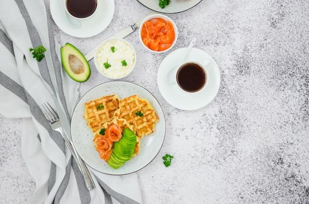 Cialde croccanti al formaggio con crema di formaggio, salmone affumicato e avocado per colazione con una tazza di caffè su un tavolo in pietra chiara.