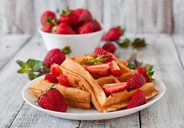 Cialde del belgio con le fragole e la menta sul piatto bianco