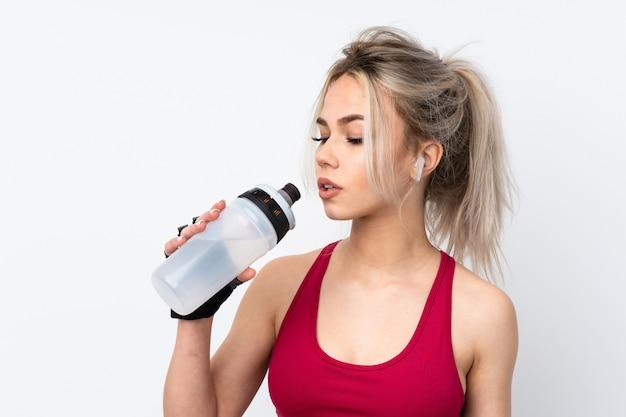 Cialde della tenuta della donna dell'adolescente sopra la parete blu isolata con la bottiglia di acqua di sport