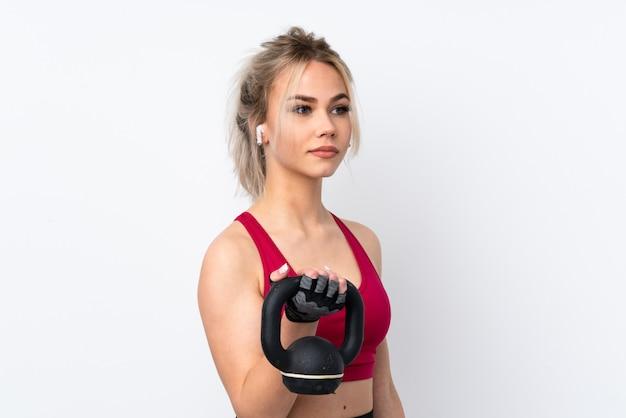 Cialde della tenuta della ragazza dell'adolescente sopra il sollevamento pesi di fabbricazione blu isolato con kettlebell
