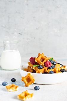 Cialde minuscole (mini) con il latte per la colazione con le bacche in una ciotola bianca su bianco