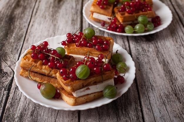 Cialde viennesi con bacche di ribes rosso e uva spina si trovano su un piatto su un tavolo di legno