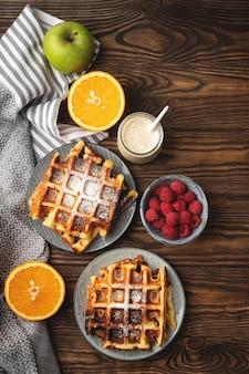 Cialde, yogurt, frutti e bacche belgi su un fondo di legno, concetto della prima colazione.
