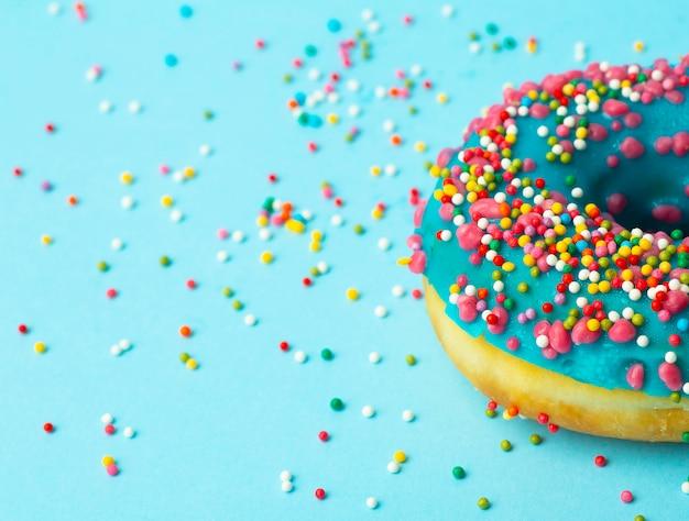 Ciambella (ciambella) di diversi colori su uno sfondo blu con spruzzi di zucchero festivo multicolore. vacanze e dolci, cottura per bambini, concetto di zucchero