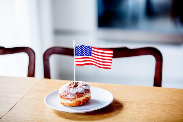 Ciambella con bandiera usa sul piatto bianco