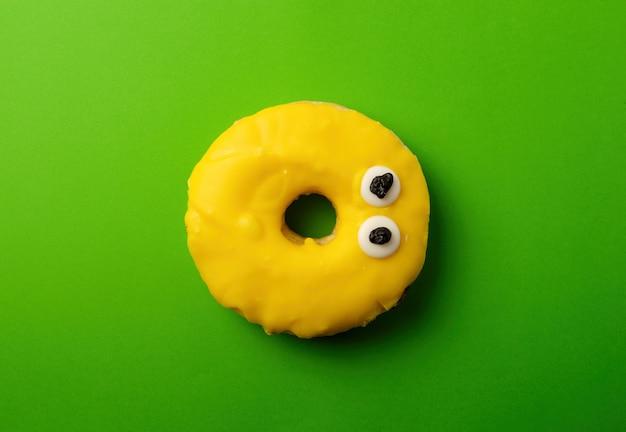 Ciambella di banana gialla rotonda su uno sfondo di grenn