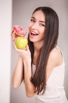 Ciambella rosa disponibila della tenuta della donna esile e mela verde