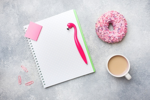 Ciambella rosa e tazza di caffè flamingo penna. vista dall'alto piatto posare.