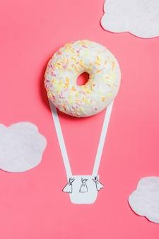 Ciambella su rosa, minimalismo alimentare creativo, ciambella a forma di aerostato in cielo con nuvole, vista dall'alto con spazio di copia, tonica