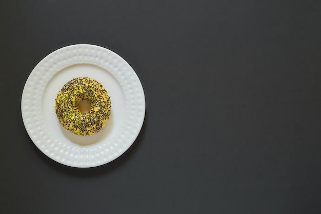 Ciambelle alla vaniglia e banana glassate con spruzzi su un piatto su pietra nera