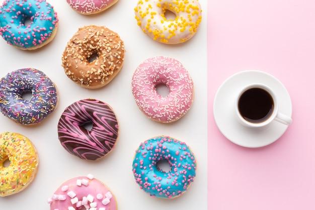 Ciambelle colorate con vista dall'alto di caffè