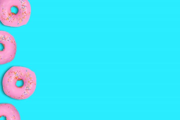 Ciambelle colorate su ciano tenero colore pastello.