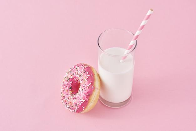 Ciambelle con bicchiere di latte su sfondo rosa