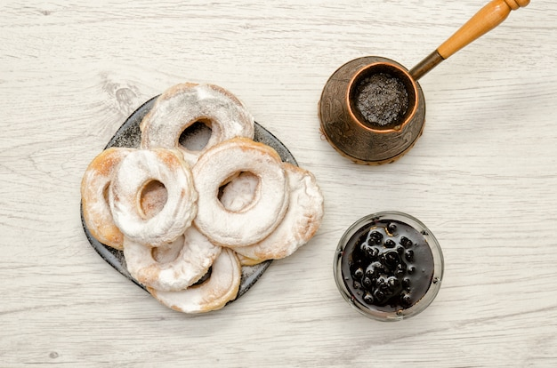 Ciambelle cosparse di zucchero a velo, caffè fresco e marmellata su un fone di legno chiaro. vista dall'alto