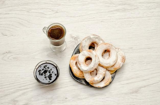 Ciambelle cosparse di zucchero a velo, caffè fresco e marmellata su un fone di legno chiaro.
