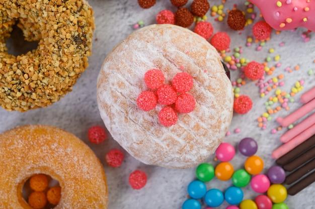 Ciambelle cosparse di zucchero a velo e caramelle su una superficie bianca.
