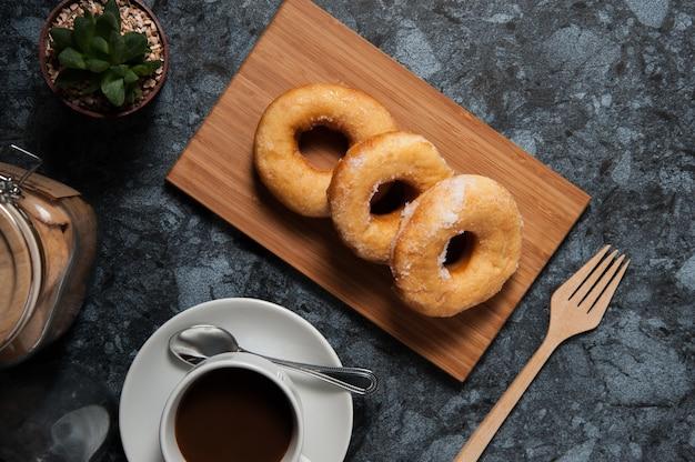 Ciambelle deliziose con glassa e tazza di caffè in zolla sulla tabella di marmo nera.