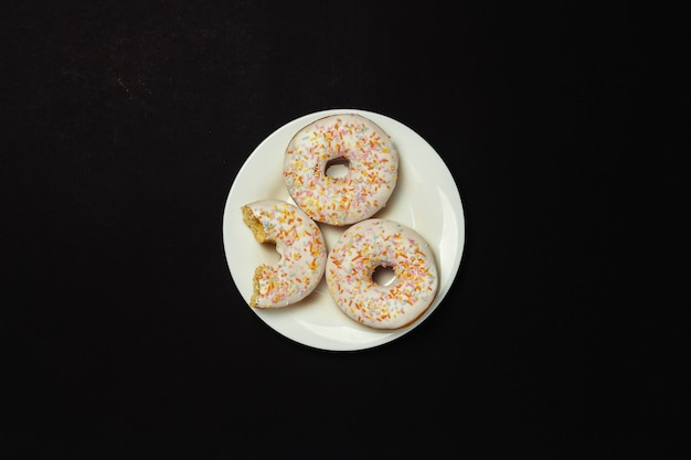 Ciambelle deliziose, dolci, fresche su un piatto bianco, fondo nero. concetto di colazione, fast food, caffetteria, prodotti da forno. vista piana, vista dall'alto.