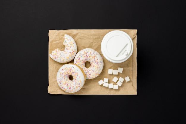 Ciambelle deliziose, dolci, fresche, tazza di caffè di carta, sacchetto di carta per alimenti da asporto, sfondo nero. concetto di colazione, fast food, caffetteria, panetteria, pranzo. vista piana, vista dall'alto.