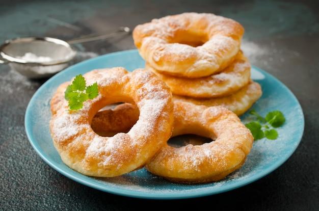 Ciambelle di ricotta alla vaniglia fritte fatte in casa su uno sfondo di cemento scuro