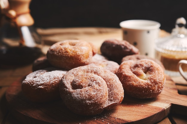 Ciambelle di serpente con zucchero a velo e caffè chemex su un tavolo di legno