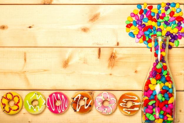 Ciambelle dolci e gelatine colorate in una bottiglia