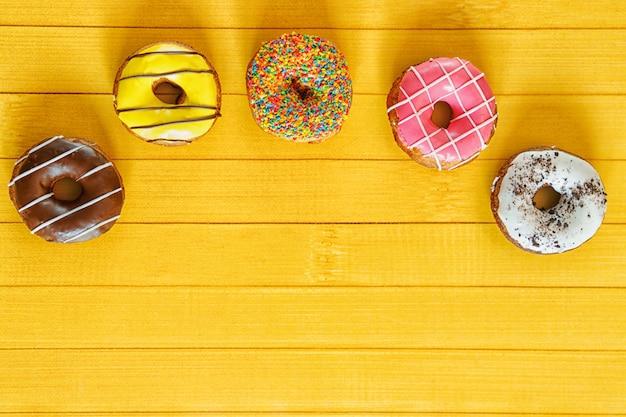 Ciambelle e confetti su un tavolo di legno.