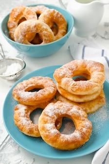 Ciambelle fritte casalinghe della ricotta della vaniglia su un fondo concreto bianco