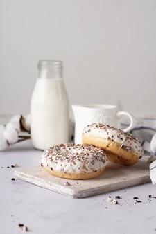 Ciambelle glassate con granelli e bottiglia di latte