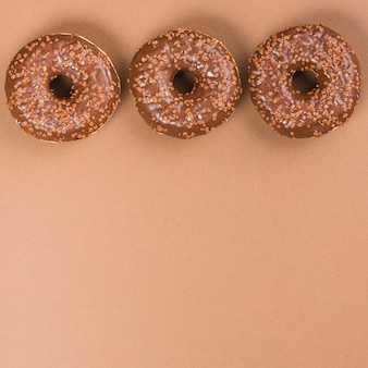Ciambelle glassate rotonde su fondo marrone