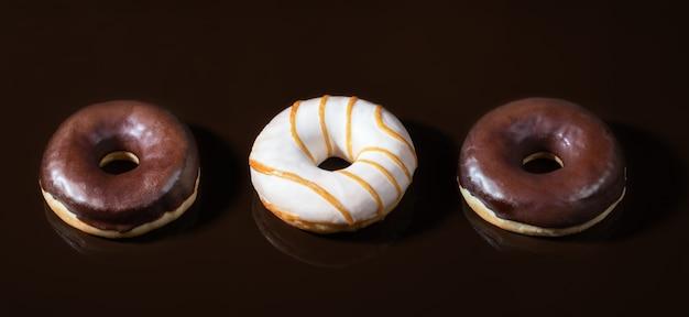 Ciambelle glassate su sfondo liscio di cioccolato fondente