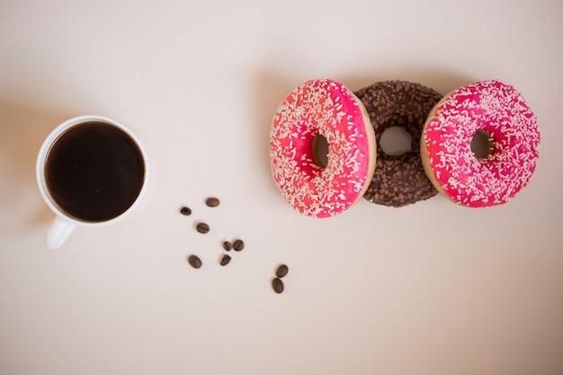 Ciambelle gustose e deliziose con glassa rosa e polvere con una tazza di caffè aromatico su una superficie bianca