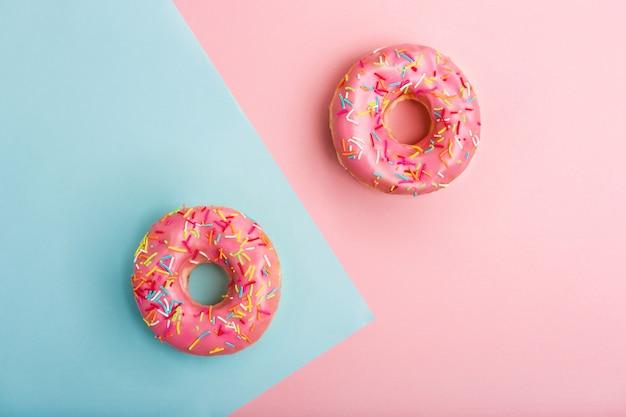 Ciambelle gustose rosa decorate con zuccherini colorati su spazio blu e rosa. ciambelle dolci minimal flat lay. disteso. vista dall'alto