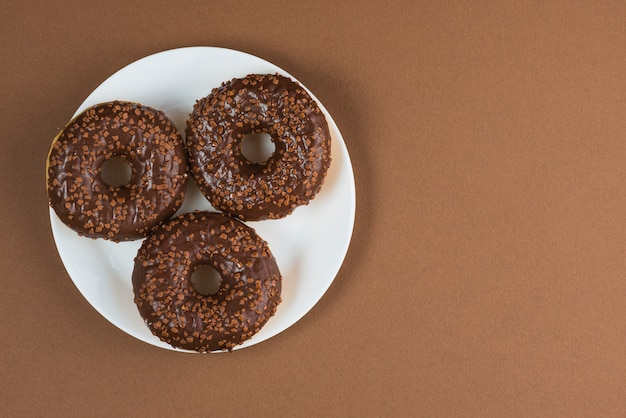 Ciambelle lustrate del cioccolato sul piatto bianco