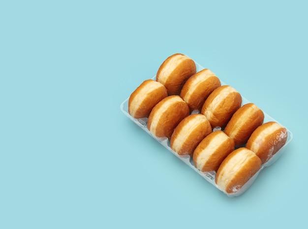 Ciambelle polacche tradizionali in una scatola su fondo blu