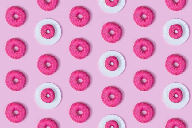 Ciambelle rosa tutto tondo su un piatto bianco