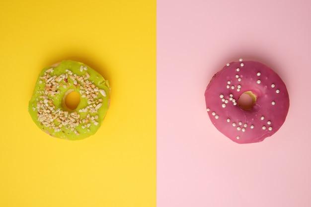 Ciambelle rotonde diverse con sprinkles su uno sfondo multicolore luminoso
