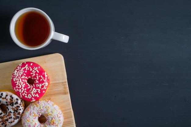 Ciambelle smaltate bianche, rosa e marroni con una tazza di tè sul lato sinistro su legno nero