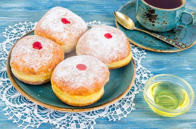 Ciambelle tradizionali con zucchero a velo e marmellata. concetto e sfondo festa ebraica hanukkah.