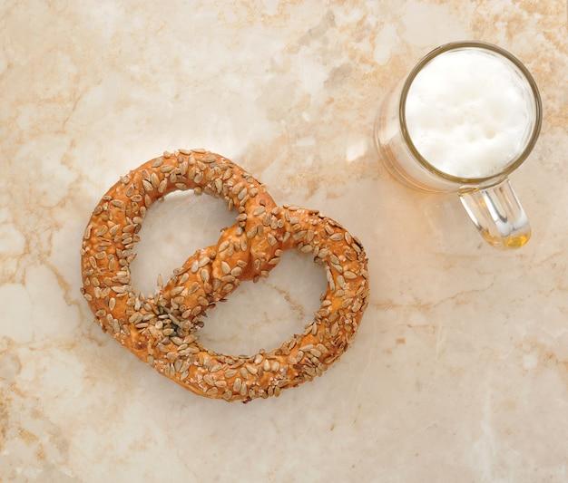 Ciambellina salata tedesca cosparsa di semi e un boccale di birra sul tavolo di marmo. vista dall'alto